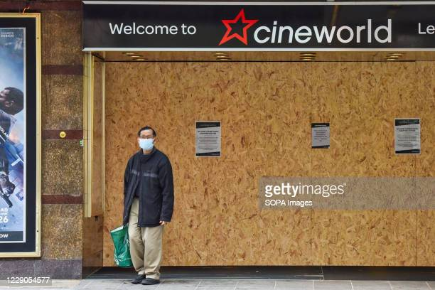A man wearing a face mask stands outside the Cineworld Cinema in London British cinema chain Cineworld announced that it's temporarily shutting...