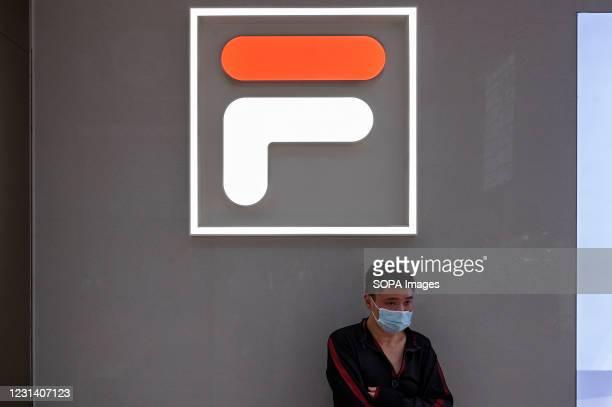 Man wearing a face mask stands outside the Italian sportswear goods brand, Fila store in Hong Kong.