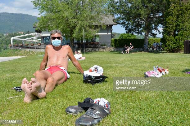 A man wearing a face mask sunbathes at the park near Lake Levico as Italy eases some lockdown restrictions on May 9 2020 in Trento Italy Italy was...