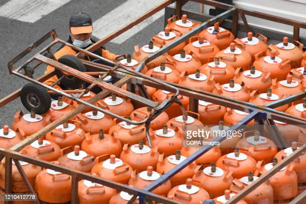 Man wearing a face mask supplies gas cylinders of butane to houses during the coronavirus threat in Madrid. Spanish Prime Minister Pedro Sanchez said...