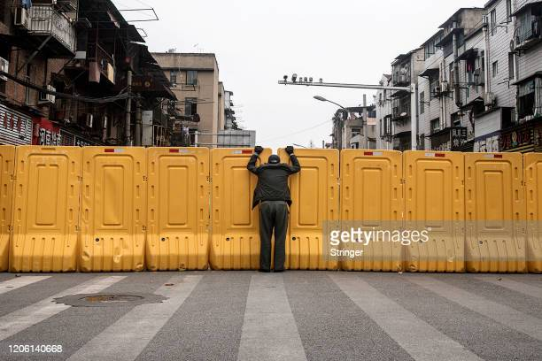 Man wearing a face mask talks to another man through a makeshift barricade wall built to control entry and exit to a residential compound on March 8,...