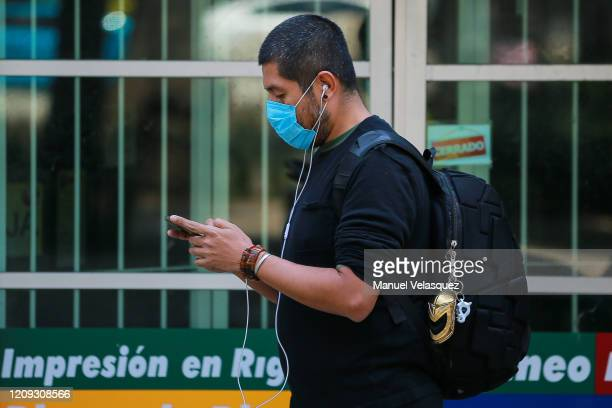 A man wearing a face mask texts on his phone on February 28 2020 in Mexico City Mexico The Secretariat of Health of Mexico announced on Friday the...