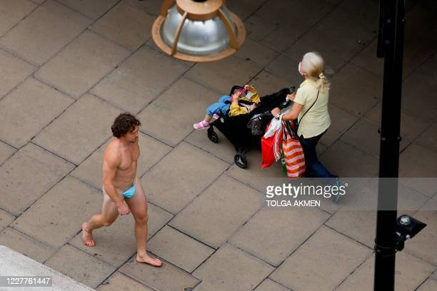 A man wearing a face mask to cover his genitals is seen walking along Oxford Street in London on July 24 after wearing facemasks in shops and...