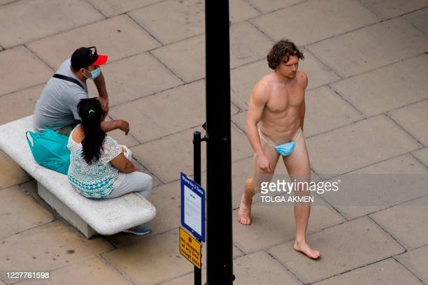 TOPSHOT A man wearing a face mask to cover his genitals is seen walking along Oxford Street in London on July 24 after wearing facemasks in shops and...