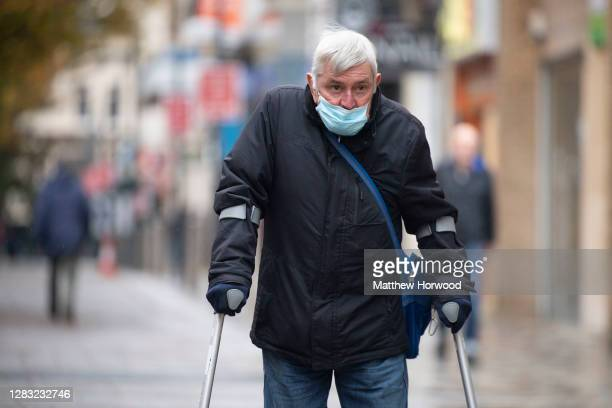 Man wearing a face mask uses crutches while walking through Newport town centre on October 31, 2020 in Newport, Wales. Wales entered a national...