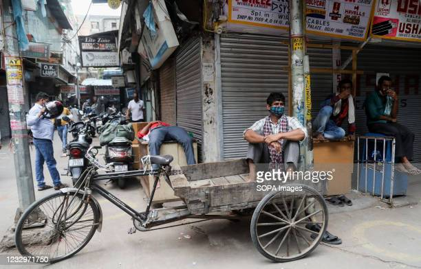 Man wearing a face mask wait for the customers outside the closed shop at Chandani Chowk main market during the lockdown in Old Delhi Chandani Chowk...