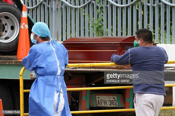 Man wearing a face mask waits for the corpse of a relative next to a health worker outside a hospital in Guayaquil, Ecuador on April 1, 2020. -...