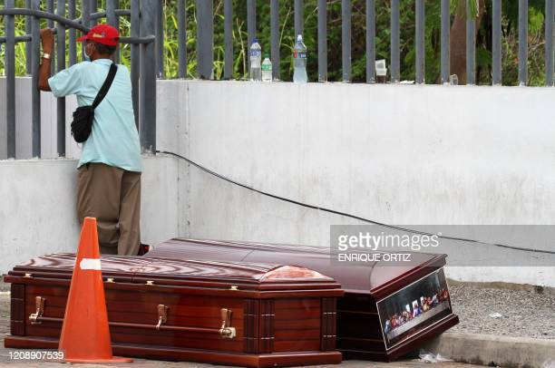 TOPSHOT A man wearing a face mask waits for the corpse of a relative outside a hospital in Guayaquil Ecuador on April 1 2020 Residents of Guayaquil...