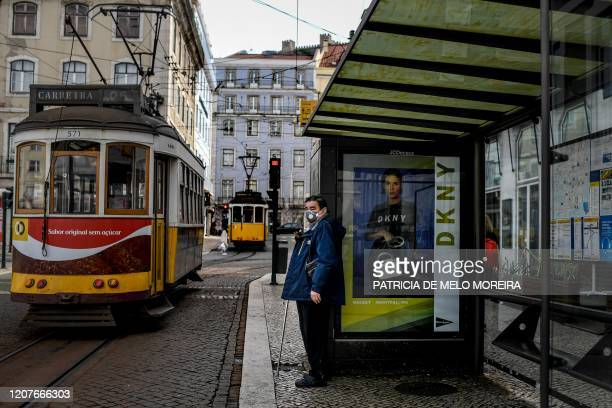 A man wearing a face mask waits for the tram in Lisbon on March 19 2020 on the first day of a state of emergency declared by the government Portugal...