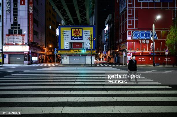 Man wearing a face mask walks across the street in the Akihabara area of Tokyo on April 17 during the COVID-19 pandemic, caused by the novel...