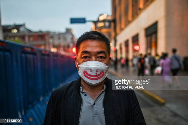 TOPSHOT A man wearing a face mask walks along a street during a holiday on May Day or International Workers' Day in Shanghai on May 1 2020 With...