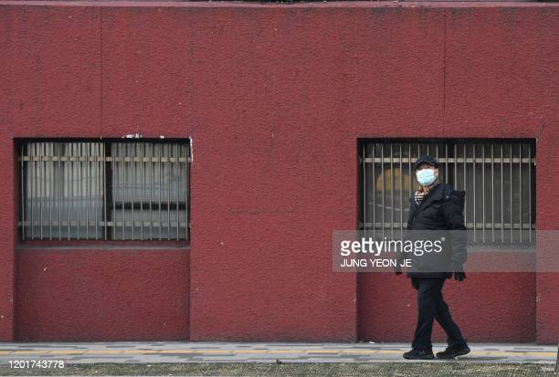 Man wearing a face mask walks along a street in Seoul on February 19, 2020. - South Korea reported 15 new confirmed cases of the novel coronavirus on...
