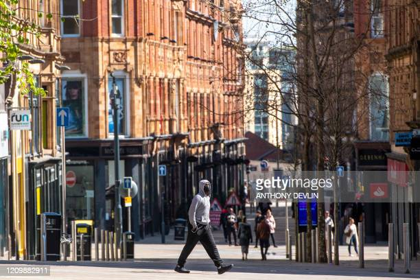 Man wearing a face mask walks along Briggate in Leeds city centre, West Yorkshire on April 14 as life in Britain continues during the nationwide...