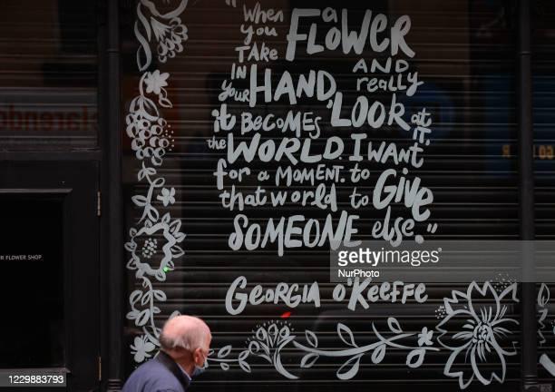 Man wearing a face mask walks by Georgia O'Keeffe's short poem painted on a shop window, in Dublin city center. Taoiseach Micheal Martin announced...