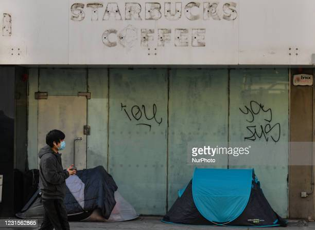 Man wearing a face mask walks by two rough sleeper's tents outside a closed Starbucks Coffee shop in Dublin city center, during Level 5 Covid-19...