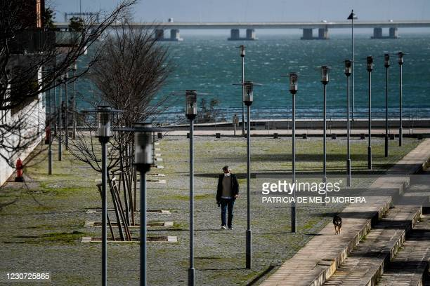 Man wearing a face mask walks his dog at Parque das Nacoes in Lisbon on January 22, 2021. - Portugal has closed schools for two weeks in a bid to...