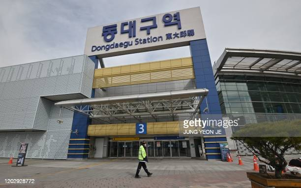 Man wearing a face mask walks in front of Dongdaegu railway station in the southeastern city of Daegu on February 24, 2020. - South Korea reported...