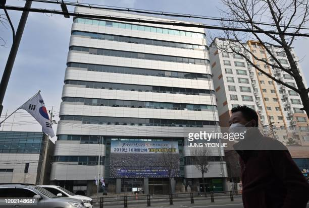 Man wearing a face mask walks in front of the Daegu branch of the Shincheonji Church of Jesus in the southeastern city of Daegu on February 21, 2020...