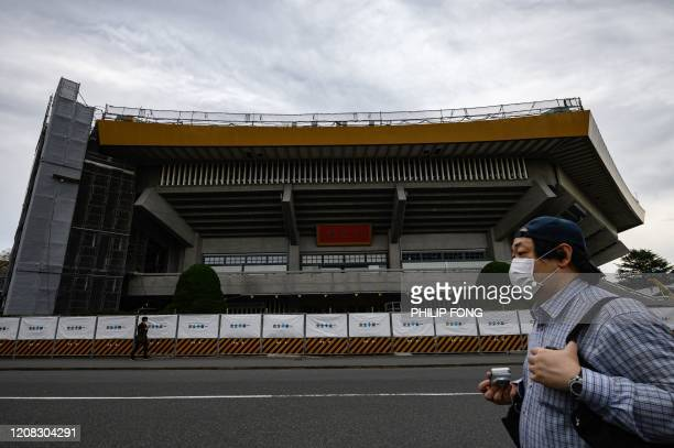 A man wearing a face mask walks in front of the Nippon Budokan one of the venues for the Tokyo 2020 Olympic Games in Tokyo on March 27 three days...