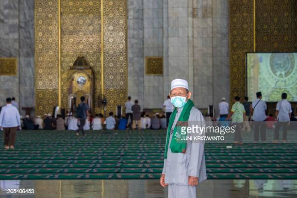 A man wearing a face mask walks inside the Al Akbar mosque before Friday prayer in Surabaya East Java province on March 6 2020 Indonesia on March 2...