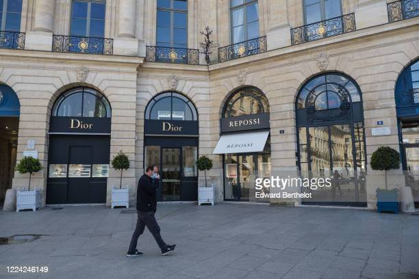 Man wearing a face mask, walks next to the Dior and Repossi stores which are open at Place Vendome on May 11, 2020 in Paris, France. France has begun...