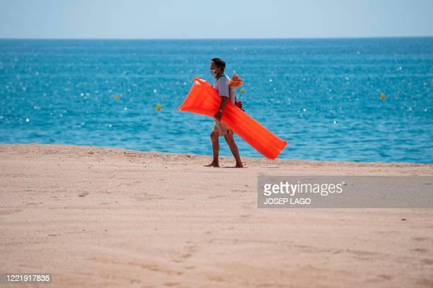 Man wearing a face mask walks on a beach in Lloret de Mar on June 22, 2020 as beaches reopen in Spain following a national lockdown to stop the...