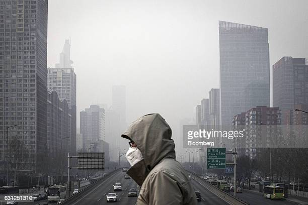 A man wearing a face mask walks on a footbridge as buildings shrouded in haze stands in the background in Beijing China on Friday Jan 6 2017 Toxic...