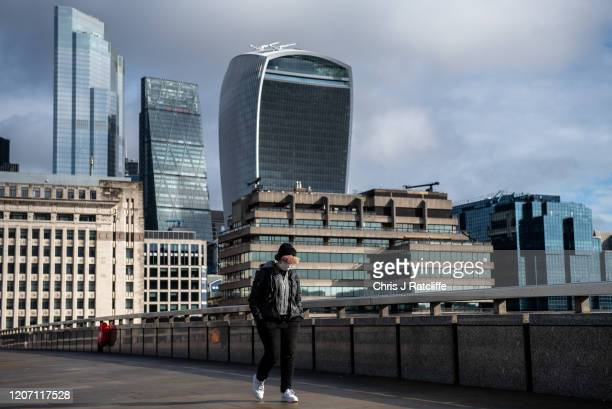 A man wearing a face mask walks over London Bridge with financial district buildings seen behind as the outbreak of coronavirus intensifies on March...