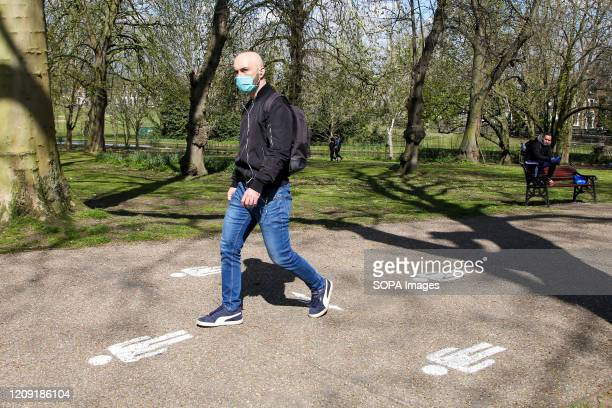 Man wearing a face mask walks over the 2 meter social distancing in Finsbury Park, north London on a warm and sunny day. The Met Office is predicting...