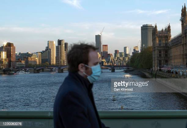 A man wearing a face mask walks over Westminster Bridge on April 20 2020 in London England The British government has extended the lockdown...
