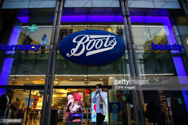 Man wearing a face mask walks past a branch of Boots on Oxford Street in central London.