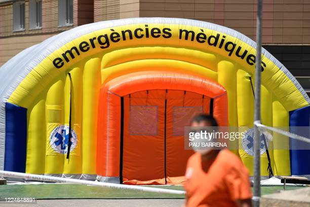 Man wearing a face mask walks past a field hospital set up for coronavirus cases outside the Arnau de Vilanova University Hospital in Lleida on July...