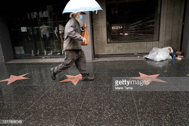 Man wearing a face mask walks past a homeless person along Hollywood Boulevard amid the coronavirus pandemic on April 9, 2020 in Los Angeles,...