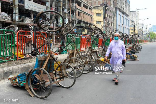 Man wearing a face mask walks past a line of inverted rickshaws on the street during a nationwide lockdown. Due to the COVID-19 pandemic, Bangladesh...