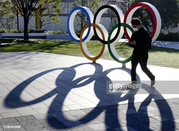 Man wearing a face mask walks past a monument depicting the Olympic rings in Tokyo's Shinjuku Ward on March 24, 2020.