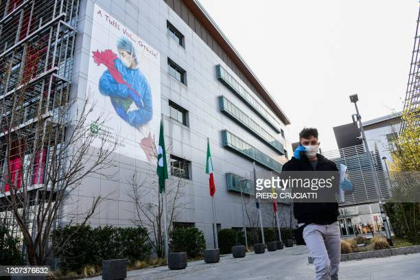 Man wearing a face mask walks past a mural by artist Franco Rivolli Art, depicting a nurse wearing a face mask, with wings behind her back and...