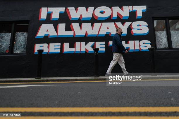 Man wearing a face mask walks past a mural by Irish artist Emmalene Blake in Dublin's city centre during level 5 COVID-19 lockdown. The theme of the...
