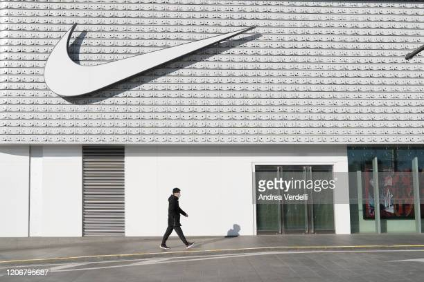Man wearing a face mask walks past a Nike store in Central Business District, Beijing, China on February 17, 2020. As many factories in the country...