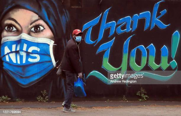 Man wearing a face mask walks past a piece of street art thanking the NHS on April 29, 2020 in London, England. British Prime Minister Boris Johnson,...