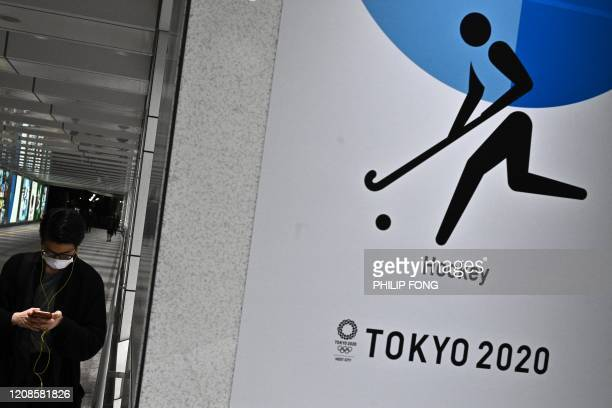 A man wearing a face mask walks past a poster of the Tokyo 2020 Olympic Games in a subway station in Tokyo on March 30 2020 Postponed Tokyo Olympics...