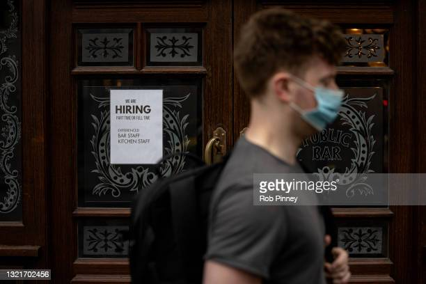 Man wearing a face mask walks past a recruitment sign in the window of a pub in Westminster on June 04, 2021 in London, England. Demand for workers...