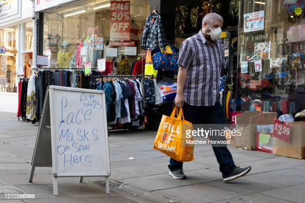 A man wearing a face mask walks past a shop selling face masks on September 14 2020 in Newport Wales First Minister of Wales Mark Drakeford has...