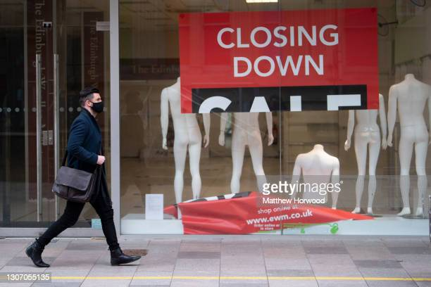 Man wearing a face mask walks past a store with a collapsed closing down sign in the window on March 4, 2021 in Cardiff, Wales. Wales went into a...
