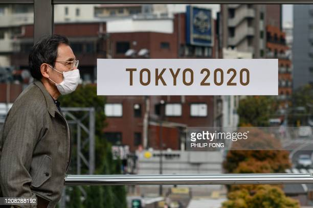 A man wearing a face mask walks past a Tokyo 2020 poster in Tokyo on March 27 three days after the historic decision to postpone the 2020 Tokyo...