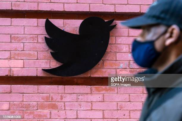 A man wearing a face mask walks past a Twitter logo outside their New York City headquarters Facebook and Twitter took steps to limit the spread of a...