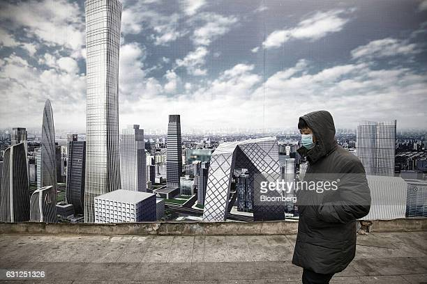A man wearing a face mask walks past an advertisement billboard showing the city's commercial district under a clear blue sky in Beijing China on...