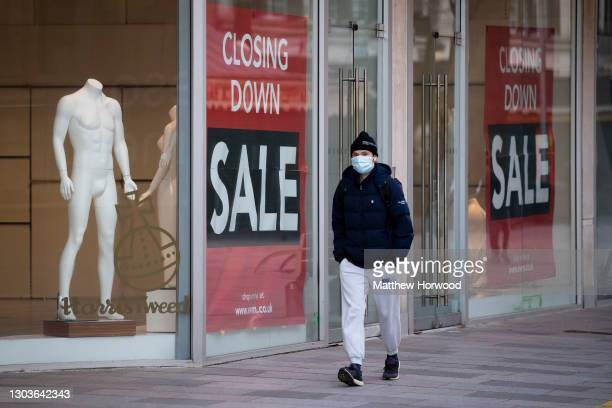 """Man wearing a face mask walks past an empty shop with a """"closing down"""" sign in the window on February 18, 2021 in Cardiff, Wales. Wales First..."""
