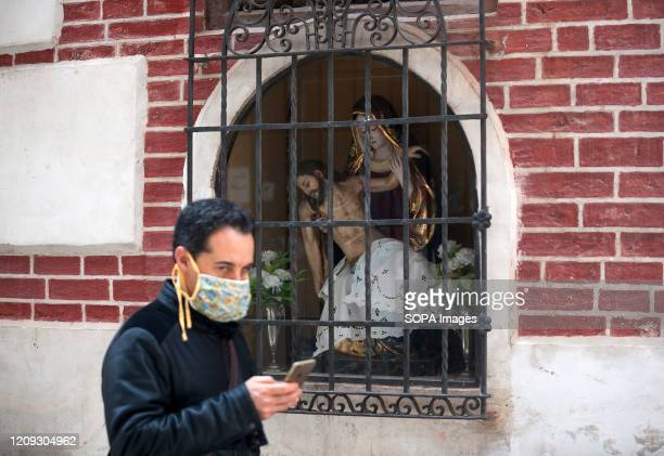 Man wearing a face mask walks past an image of Christ during a Holy Monday in downtown city. The traditional Easter celebration has been cancelled in...