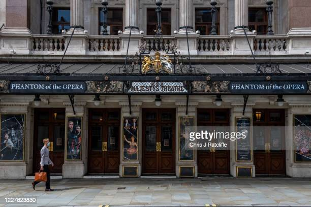 Man wearing a face mask walks past Her Majestys Theatre, home to Phantom of the Opera, on July 29, 2020 in London, England. Phantom of the Opera,...