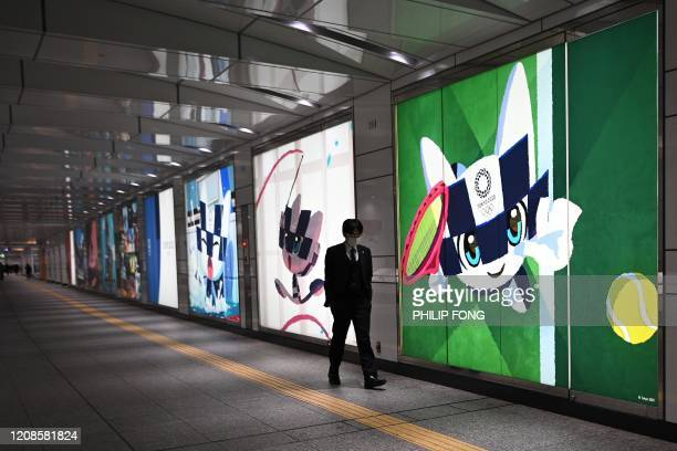 A man wearing a face mask walks past posters of the Tokyo 2020 Olympic Games in a subway station in Tokyo on March 30 2020 Postponed Tokyo Olympics...